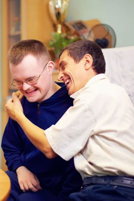 Zwei Freunde mit Behinderung lachen gemeinsam