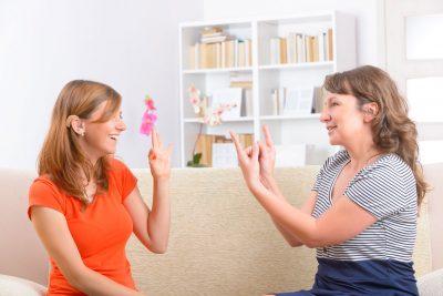 Zwei fröhliche gehörlose Frauen reden in Zeichensprache miteinander