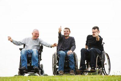 Drei fröhliche junge Männer im Rollstuhl