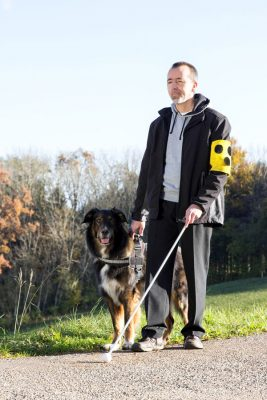 Ein blinder Mann geht mit seinem Blindenhund spazieren