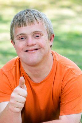 Fröhlicher junger Mann mit Down-Syndrom in orangem T-Shirt